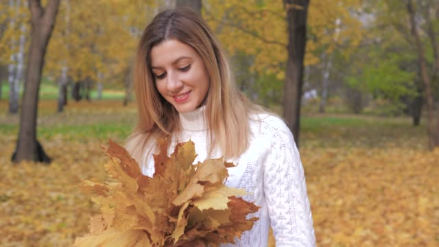 Movement Around Woman Holding Bouquet Of Fallen Yellow Leaves In Autumn Park video