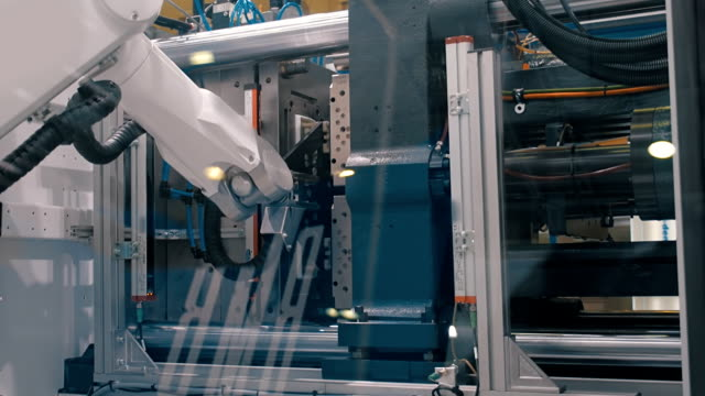 Movement molds, robot arm manipulator takes the finished product and stock them video