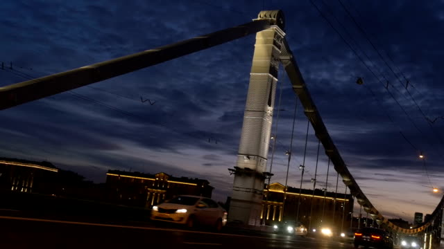 movement of cars in the evening, through a large beautiful bridge. - rzeka moskwa filmów i materiałów b-roll