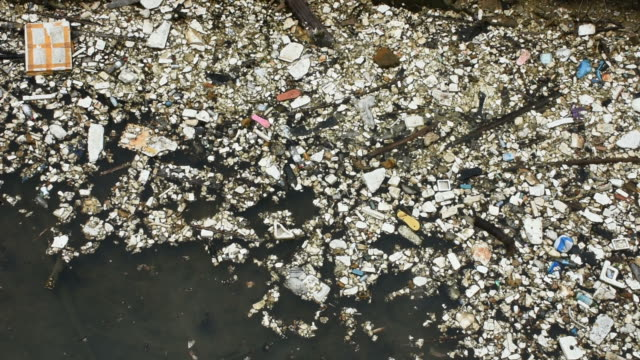 Movement of many garbage on surface of water in pond at outdoor
