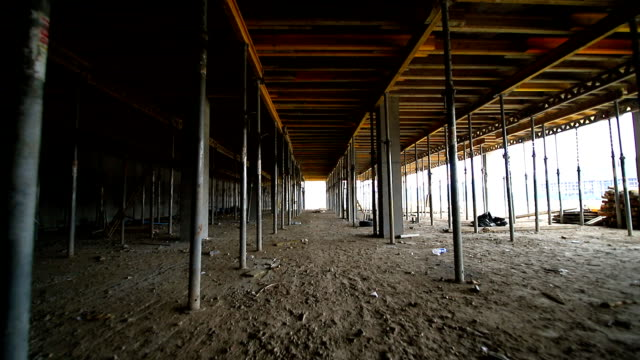 Movement of the camera between the building supports that support concrete structures. Unfinished floor on the construction site Movement of the camera between the building supports that support concrete structures. Unfinished floor on the construction site. prop stock videos & royalty-free footage