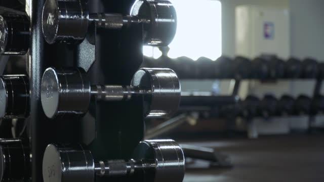 stockvideo's en b-roll-footage met beweging van de camera op de plank met behulp van halters - fitnessapparaat
