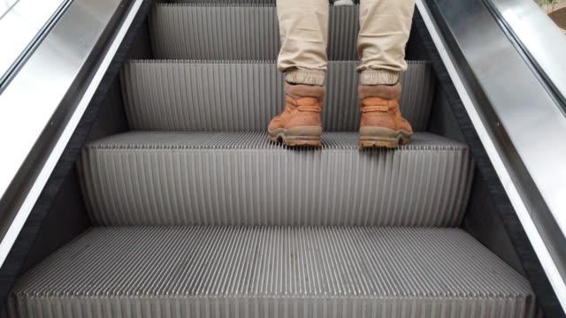 Movement of the escalator. The man walks up the escalator. video