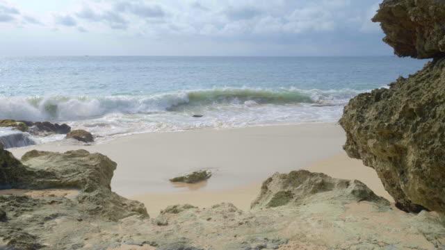 en rörelse på tropisk strand med vulkanisk sten närbild och sand filmade handhållen - turkos blå bildbanksvideor och videomaterial från bakom kulisserna