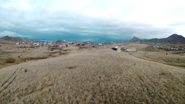movement towards the horizon line above the valley with houses - badawczy statek kosmiczny filmów i materiałów b-roll