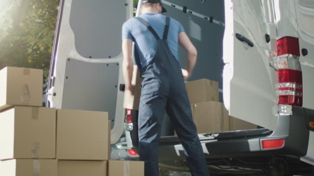 mover lädt seine van mit kartons. - briefkasten stock-videos und b-roll-filmmaterial