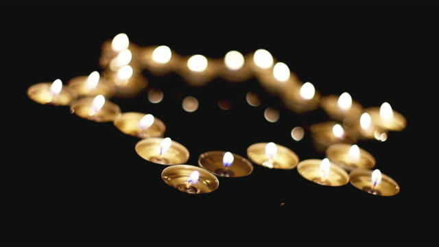 Movie of burning candles in the shape of a star of david on a black background. Bokeh on dark backdrop, shallow depth of field video