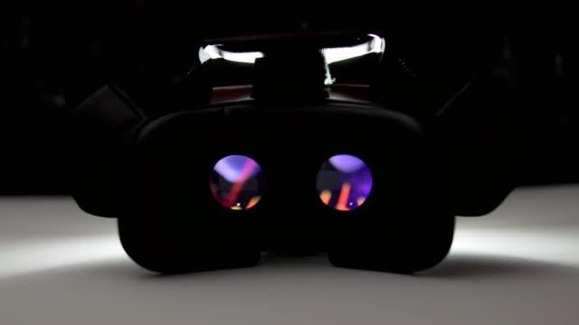 movie playing inside virtual reality device on white table at night indoor. 4k - оптический инструмент стоковые видео и кадры b-roll