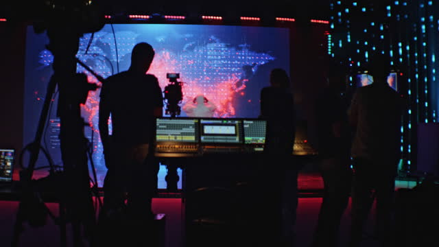 Movie set in silhouettes. Large screen with projection in background