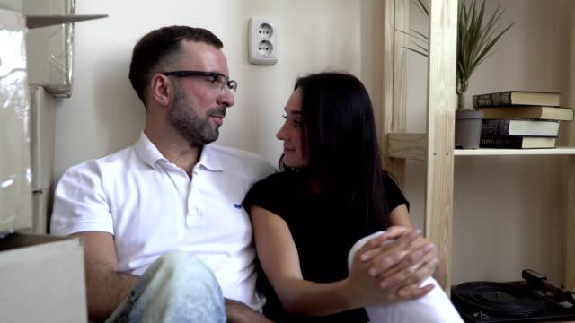 stockvideo's en b-roll-footage met een jong gezin verhuizen naar een nieuw appartement. man en vrouw zittend op de vloer in de buurt van de planken en vakken van dingen. een man in bril en een wit t-shirt knuffels zijn vrouw en glimlacht gelukkig bij haar - wit t shirt