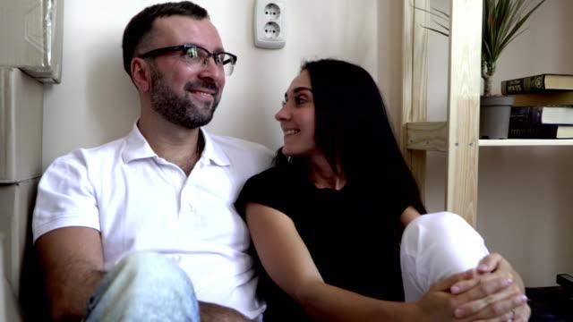 stockvideo's en b-roll-footage met een jong gezin verhuizen naar een nieuw appartement. man en vrouw zittend op de vloer in de buurt van de planken en vakken van dingen. een man in de bril en een wit t-shirt glimlacht vreugdevol op zijn vrouw. een paar in liefde is blij - wit t shirt