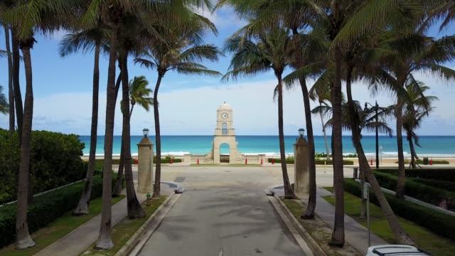 vídeos de stock e filmes b-roll de moving aerial footage along worth avenue, palm beach, fl during covid-19 - climate clock