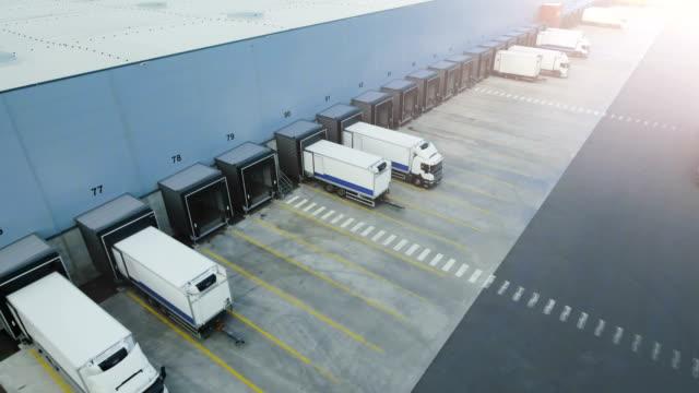 moving aerial side shot of industrial warehouse loading dock where many truck with semi trailers load/ unload merchandise. - rozładowywać filmów i materiałów b-roll