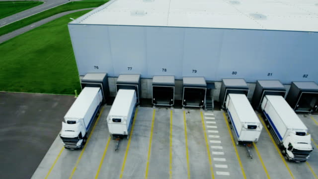 moving aerial side shot of industrial warehouse loading dock where many truck with semi trailers load/ unload merchandise. - logistica video stock e b–roll
