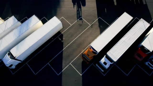 Moving Aerial Top View of Parked Semi Trucks with Cargo/ Refrigerator Trailers Standing on their Dedicated Parking Places. video