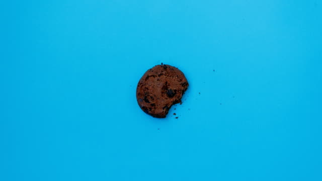 Moving and disappearing chocolate chip cookie Moving and disappearing chocolate chip cookie on blue background, stop motion. 4K. Abstract colorful animation. Food, eating concept obsolete stock videos & royalty-free footage