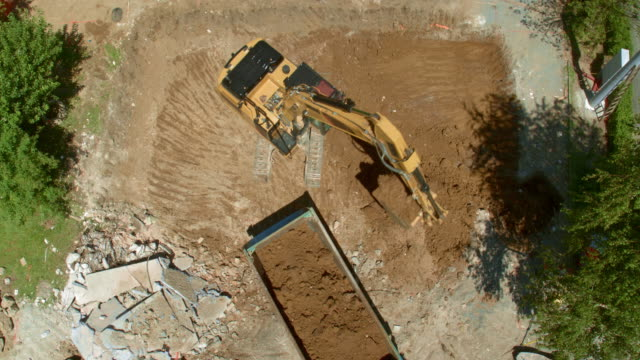 AERIAL Moving away from the excavator loading the truck with soil dug out at the construction site Aerial shot rising above the excavator loading a truck with excavated soil at the sunny construction site. Shot in Slovenia. construction vehicle stock videos & royalty-free footage