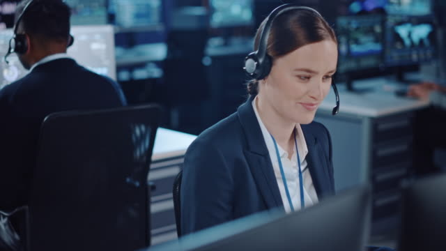 moving camera from a middle aged bearded technical support specialist to a young beautiful female colleague talking on a headset while working on a computer in control room filled with displays. - call center стоковые видео и кадры b-roll