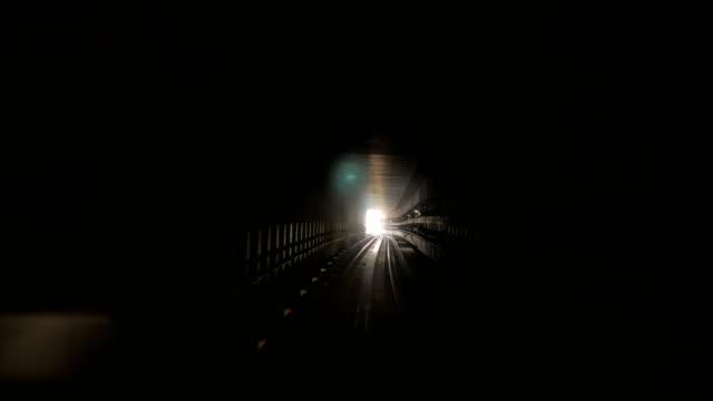 moving camera in dark railway tunnel toward bright light in the end - tunnel video stock e b–roll