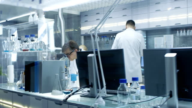Moving Camera Shot of High Tech Ultra Modern Laboratory with Scientists Conducting experiments, Working on Computers and Mixing Chemicals. video