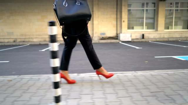moving camera shot of the feet of one businesswoman walking on sidewalk in the morning - личный аксессуар стоковые видео и кадры b-roll