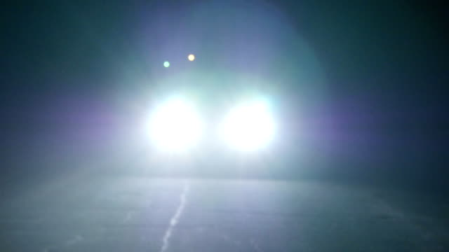 Moving car with lights at night. Car going on empty night road. In total darkness seen only the bright light of car headlights. Moving car with lights at night. Car going on empty night road. In total darkness seen only the bright light of car headlights. car accident stock videos & royalty-free footage