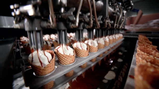 Moving conveyer with ice-cream cones. Filling ice cream in cones, cup video