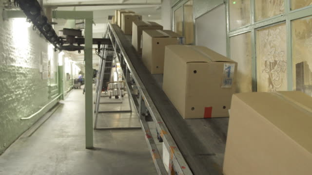Moving conveyor belt with cardboard boxes along corridor in workplace video
