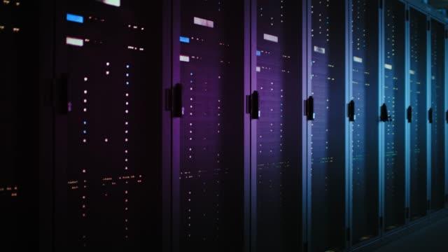 flytta data skott av mörka data center med flera rader av fullt fungerande serverrack. modern telekommunikation, cloud computing, artificiell intelligens, databas, superdator. neonljus - server room bildbanksvideor och videomaterial från bakom kulisserna
