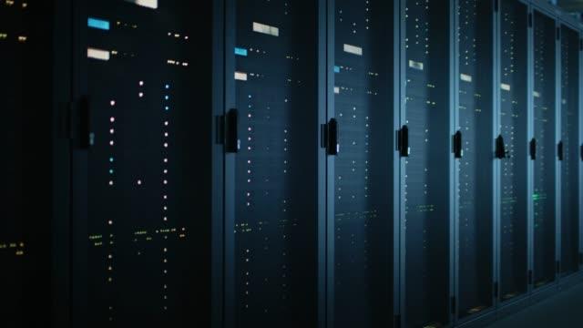 複数行と完全に運用サーバー ラックの暗いデータ センターのデータ ショットを移動します。現代の通信、クラウド ・ コンピューティング、人工知能、データベース、スーパー コンピュー� - スーパーコンピューター点の映像素材/bロール