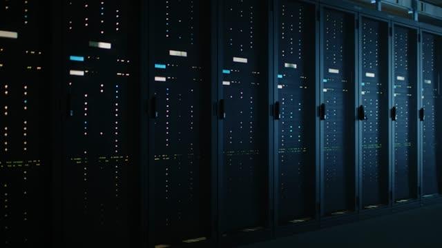 stockvideo's en b-roll-footage met het verplaatsen van gegevens schot van dark data center met meerdere rijen met volledig operationeel server racks. moderne telecommunicatie, cloud computing, kunstmatige intelligentie, database, supercomputer - datacenter