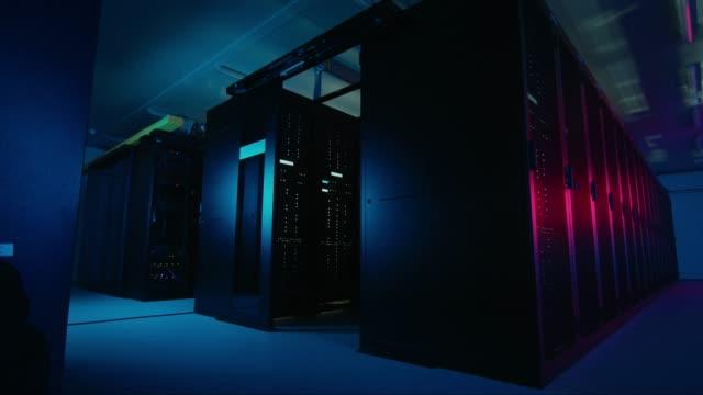 flytta data skott av neon mörka data center med flera rader av fullt fungerande serverrack. moderna begreppet telekommunikationer, cloud computing, artificiell intelligens, databas, superdator - server room bildbanksvideor och videomaterial från bakom kulisserna