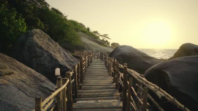 povショットを移動台車木道の岸に海と大きな岩の間に。 - リゾート点の映像素材/bロール