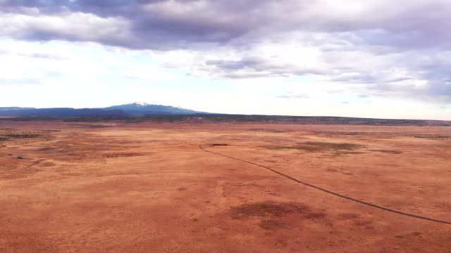 Moving Drone Footage of the Utah Desert with the Majestic LaSal Mountains of Southeastern Utah near Moab in the Background at Dusk Under a Dramatic Cloudscape