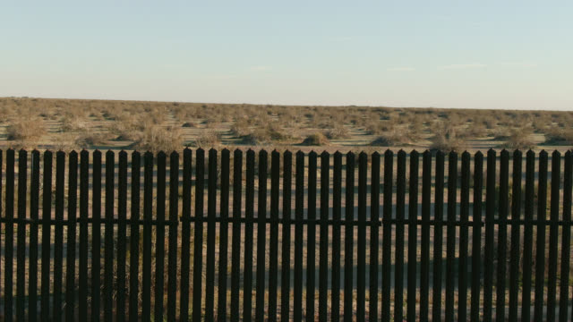 Moving Drone Shot of Looking through the Steel-Slat Border Wall (on the US side) between Mexico and the United States to the Desert on the Other Side on a Clear, Sunny Afternoon