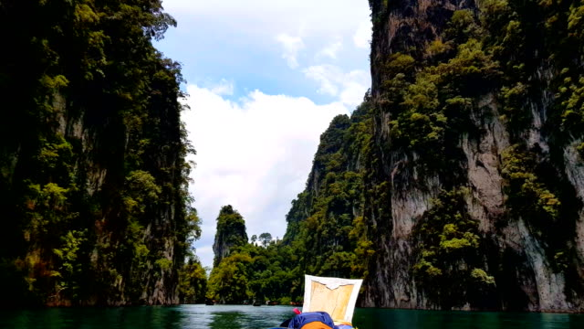 moving follow boat with beautiful mountains lake river sky and natural attractions in ratchaprapha dam at khao sok national park, surat thani province, thailand. - phuket video stock e b–roll