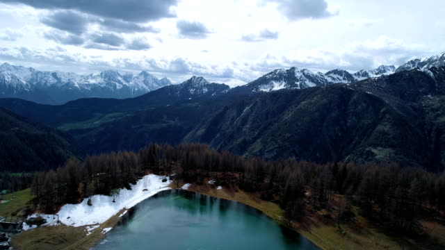 moving forward above village and blue lake to pine larch woods forest and snowy mountain in autumn.Fall Alps outdoor nature scape mountains wild aerial establisher.4k drone flight establishing shot video