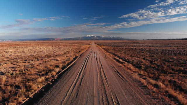vídeos de stock e filmes b-roll de moving forward aerial drone shot of a vanishing point dirt road with mountains in the background outside of moab, utah with desert plains on either side underneath a blue sky at sunset/sunrise - caminho adiante