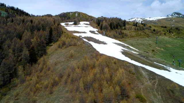 moving forward discovering above pine larch woods forest and snowy ski track in mountain in autumn. Fall Alps outdoor nature scape mountains wild aerial establisher.4k drone flight establishing shot video