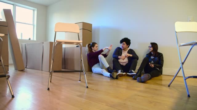 Moving in! The group of young friends, teenager Caucasian white girls, sisters, and Latinos teenager boy, sitting on the floor in the empty living room filled with cardboard boxes, in the new house. video