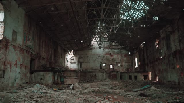 Moving inside ruined and abandoned large creepy industrial factory warehouse hangar