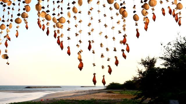 vídeos de stock, filmes e b-roll de movendo-se de conchas móveis do telhado da brisa suave no fundo borrado praia de suspensão - mobile
