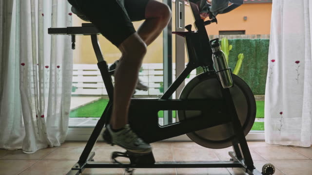 Moving out video of man working out on exercise bike at home Moving out slow motion video of man working out on exercise bike at home during pandemic. exercise bike stock videos & royalty-free footage