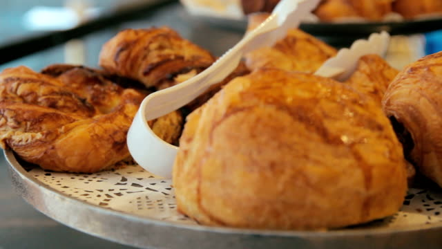 moving panning right shot of many sweet crispy croissants and rugelach placed on a tray in a cafe or bakery shop - impasto video stock e b–roll