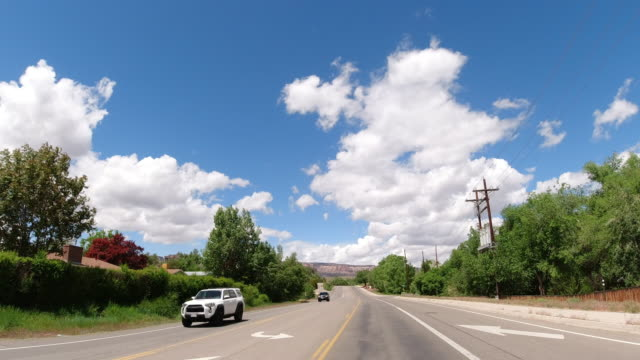 Moving Process Plate of a Vehicle Driving along a Main Road Lined with Trees with the Colorado National Monument in the Background under a Partly Cloudy Sky