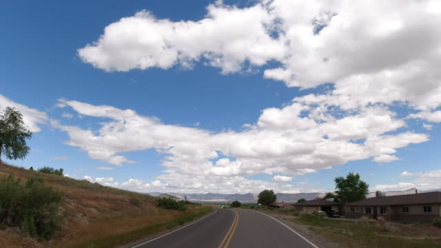 Moving Process Plate of a Vehicle Driving Down (Leaving) the Colorado National Monument and Heading Toward Grand Junction, Colorado and the Bookcliffs Mountain Range under a Partly Cloudy Sky