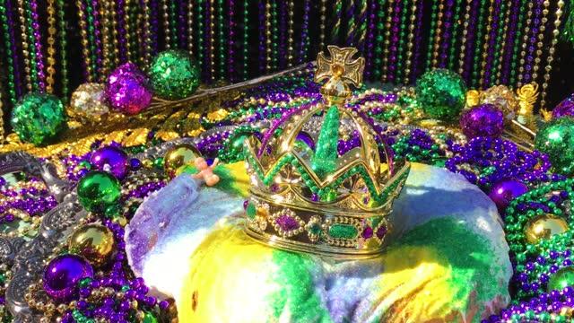 vidéos et rushes de ombres mobiles au-dessus du gâteau roi de mardi gras avec la couronne et le bébé minuscule entouré par des perles colorées - galette des rois