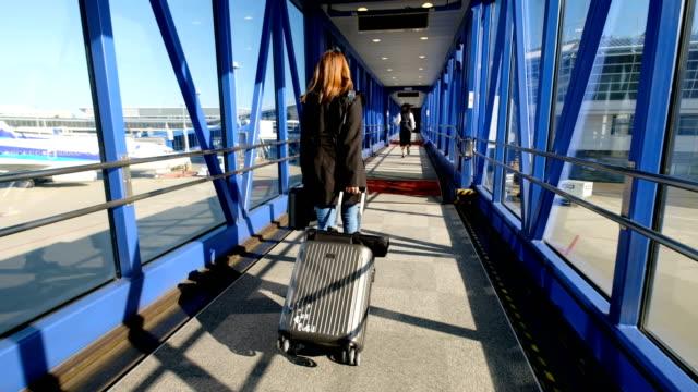 4k moving shot: asian woman dragging luggage in aircraft docking at international airport. when she arrived the destination - wchodzić na pokład filmów i materiałów b-roll