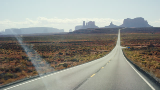 Moving Shot from the Perspective of a Vehicle of a Road while Driving Down a Highway/Interstate in the Desert of Arizona on a Bright, Sunny Day with Mountains and Rock Formations in the Distance