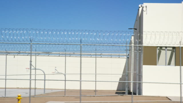vidéos et rushes de moving shot of a prison in phoenix, arizona with a barbed wire chainlink fence surrounding an outdoors basketball court on a sunny morning - prison